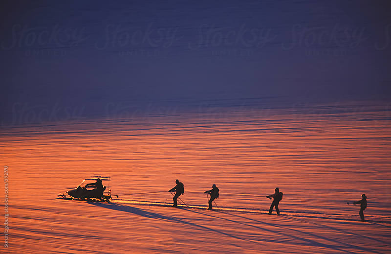 Skiers and snowboarders being pulled by snowmobile on Appusuit Glacier in Greenland by Soren Egeberg for Stocksy United