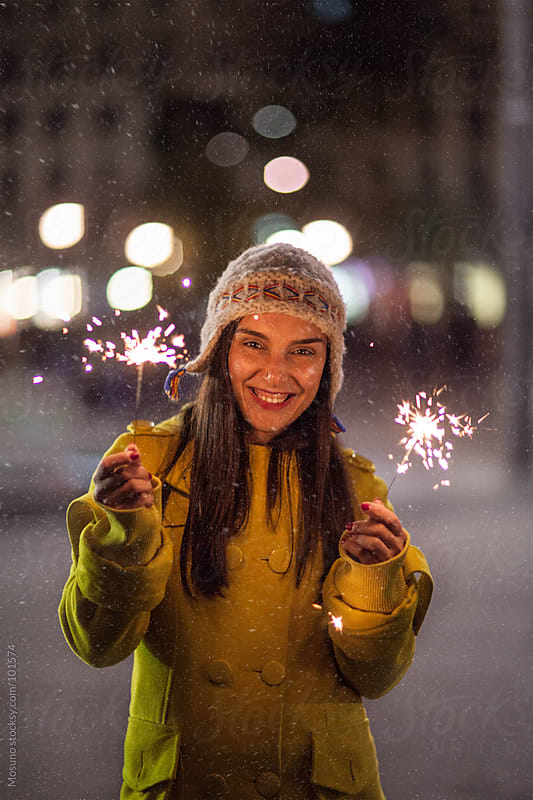 Woman Holding Sparklers on a Cold Snowy Night by Mosuno for Stocksy United