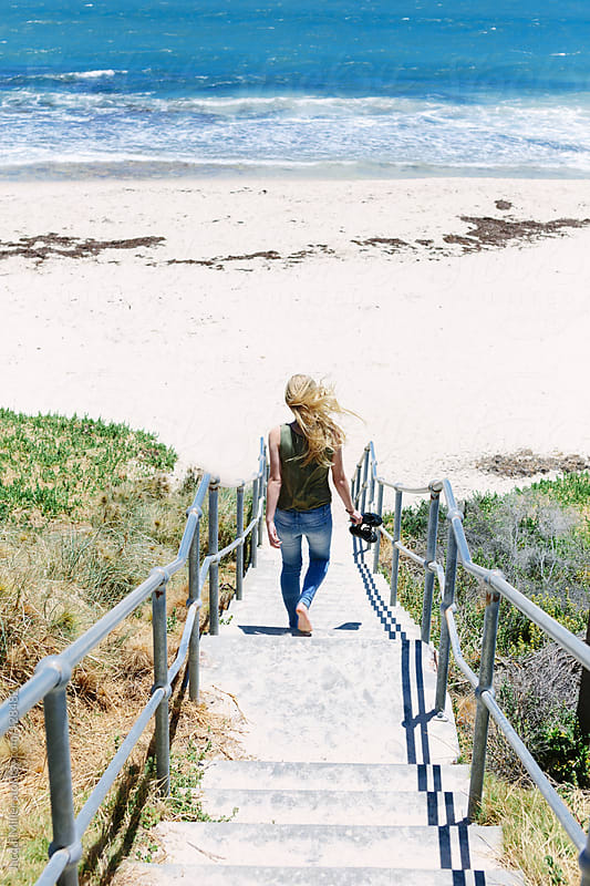 Teenage girl walking down a flight of stairs to the beach by Jacqui Miller for Stocksy United
