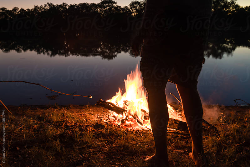 roasting marshmallows over a campfire at night by Gillian Vann for Stocksy United