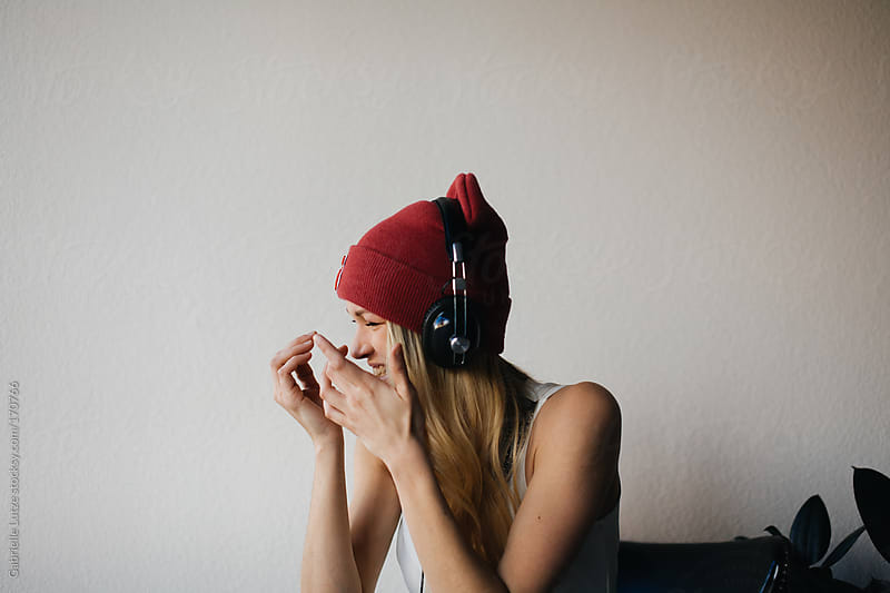 Pretty Blond Woman in a Beanie and Headphones Listening to Music  by Gabrielle Lutze for Stocksy United