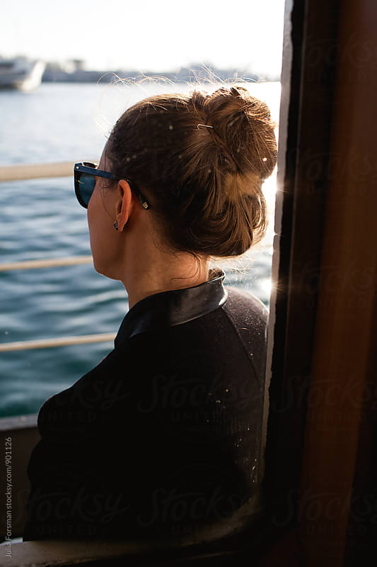 Young woman with her hair in a bun looks out over water while travelling by boat. by Julia Forsman for Stocksy United