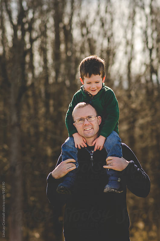 Man carrying smiling boy on his shoulders by Lindsay Crandall for Stocksy United