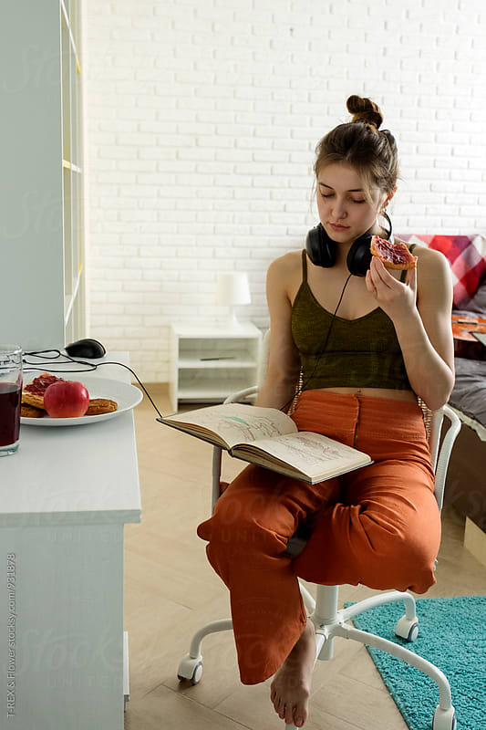 Woman reading book while holding piece of pizza by Danil Nevsky for Stocksy United