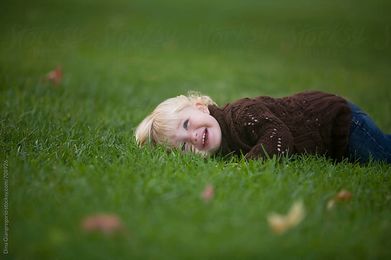 Toddler Blonde Girl Laying In Grass Laughing by Dina Giangregorio for Stocksy United