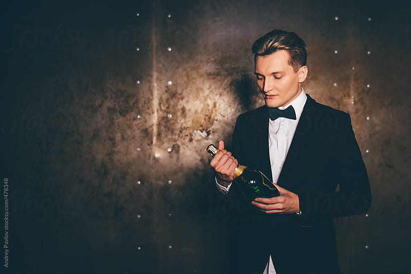 Handsome men dressed in a suit with bottle of champagne by Andrey Pavlov for Stocksy United