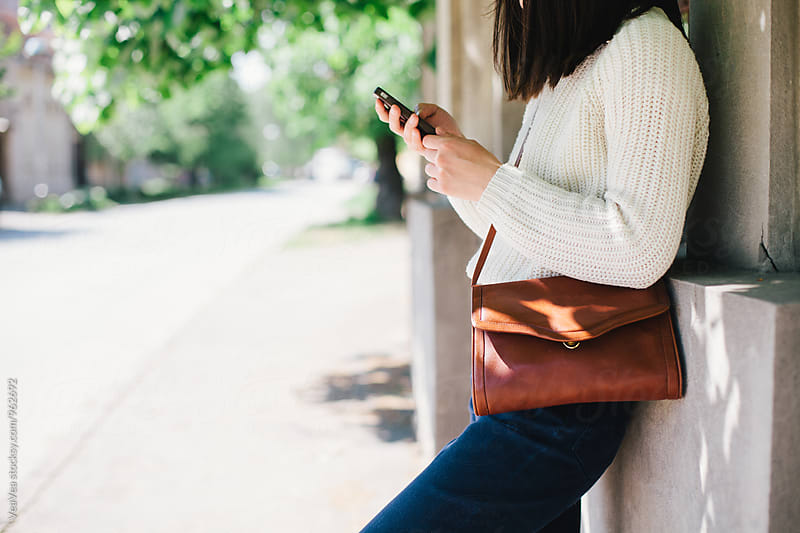 Woman using her mobile phone in the street by VeaVea for Stocksy United