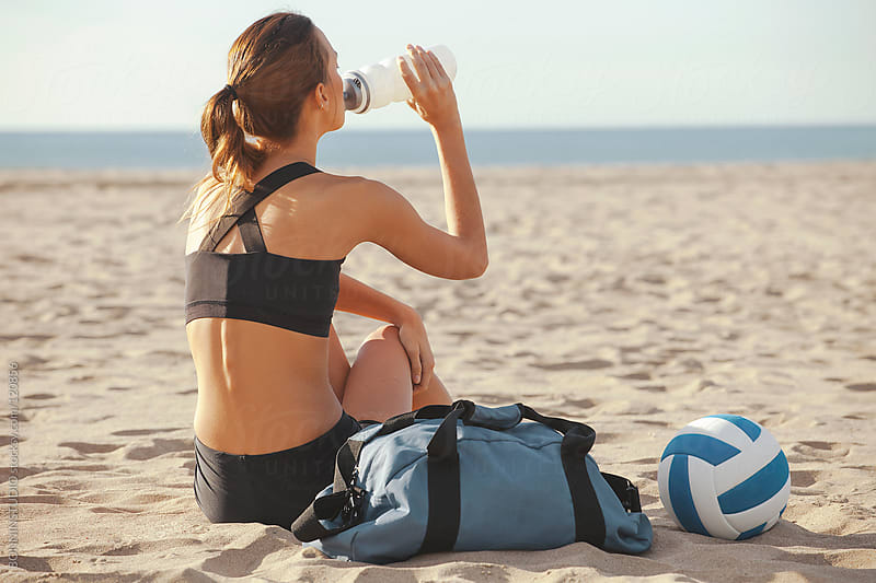 Sporty woman resting after hard beach volleyball game. by BONNINSTUDIO for Stocksy United