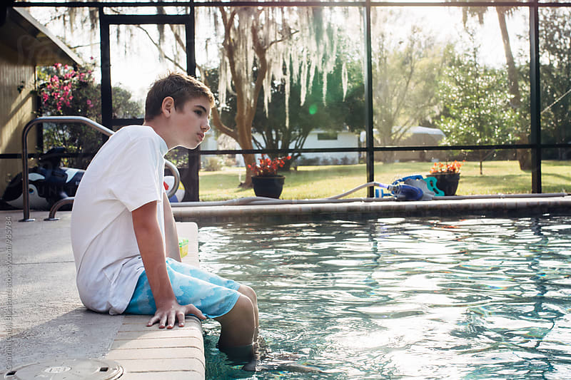 Young boy hanging out by a pool by Gabriel (Gabi) Bucataru for Stocksy United