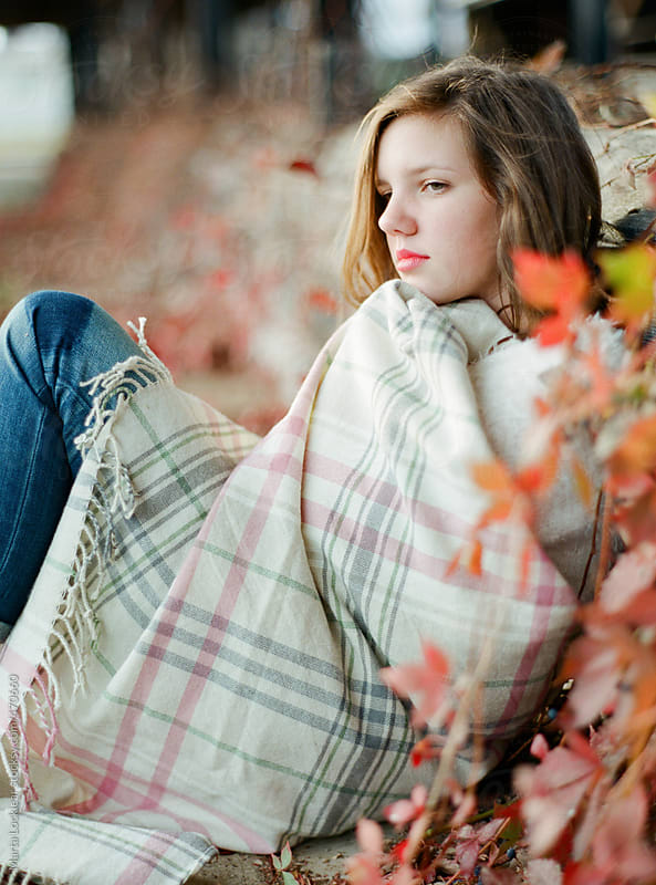 Portrait of a teen girl leaning on a wall of fall leaves by Marta Locklear for Stocksy United