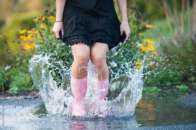 Woman with pink rain boots splashes in a puddle by Brian McEntire for Stocksy United