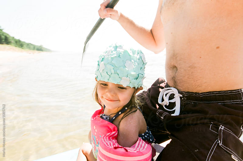 father and daughter paddling on lake by Maria Manco for Stocksy United