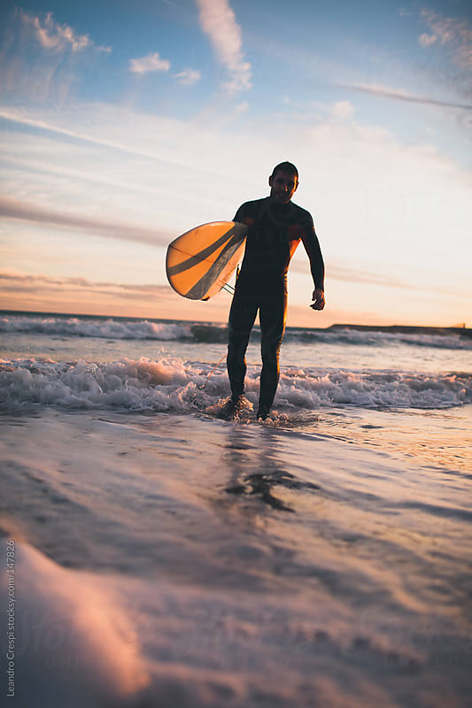Portrait of a surfer with board going out the water by Leandro Crespi for Stocksy United
