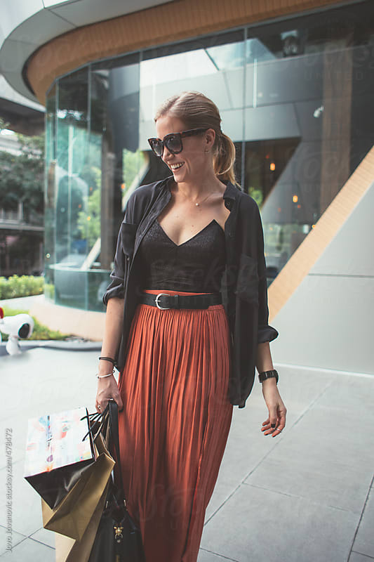 Fashionable blonde woman and her shopping, smiling in the city by Jovo Jovanovic for Stocksy United