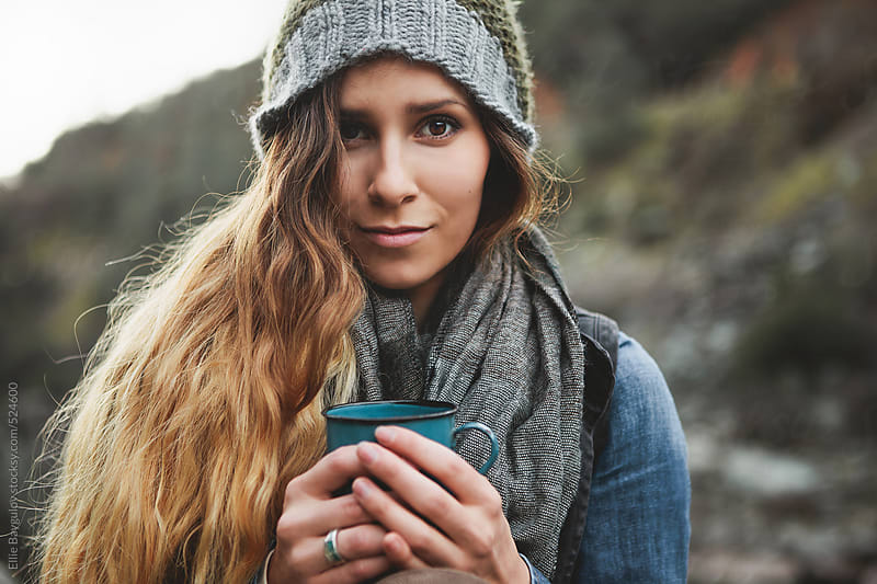 Woman holding a warm drink by Ellie Baygulov for Stocksy United