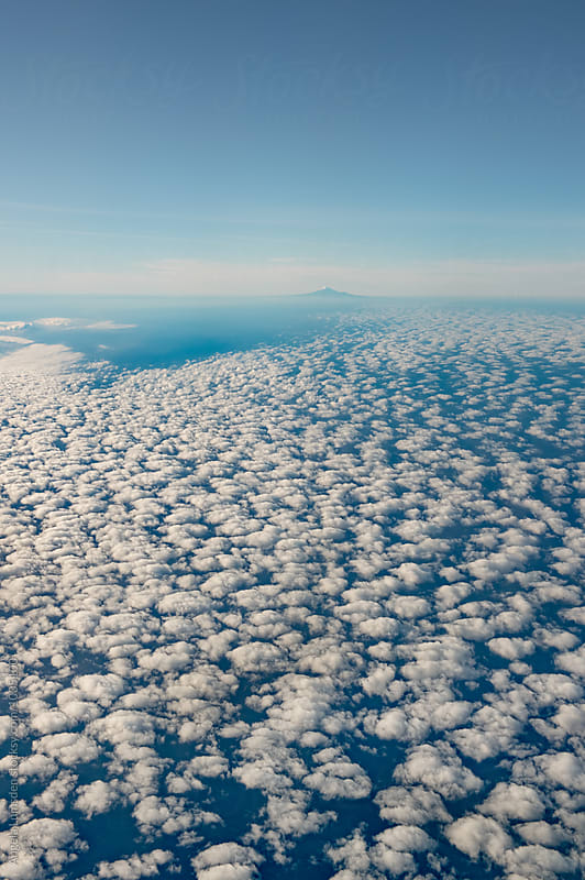Fluffy clouds and Mt Taranaki, descending into Auckland early in the morning by Angela Lumsden for Stocksy United