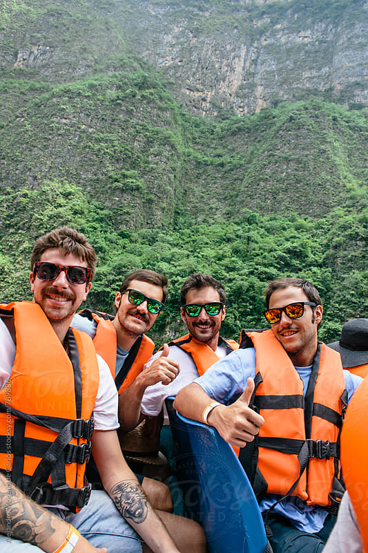 Four young men with life jackets in a boat showing a thumbs up with a lush green hill of a valley behind by Alejandro Moreno de Carlos for Stocksy United