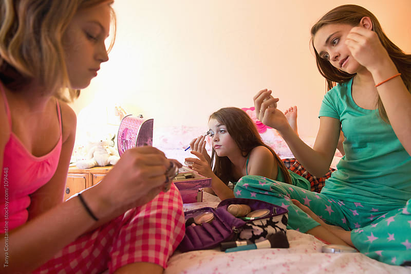 three tweens putting on make-up in their pajamas by Tanya Constantine for Stocksy United