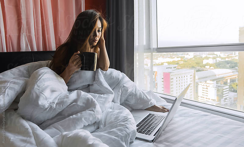 Pretty Asian woman drinking coffee in bed and surfing on web. by Marko Milanovic for Stocksy United