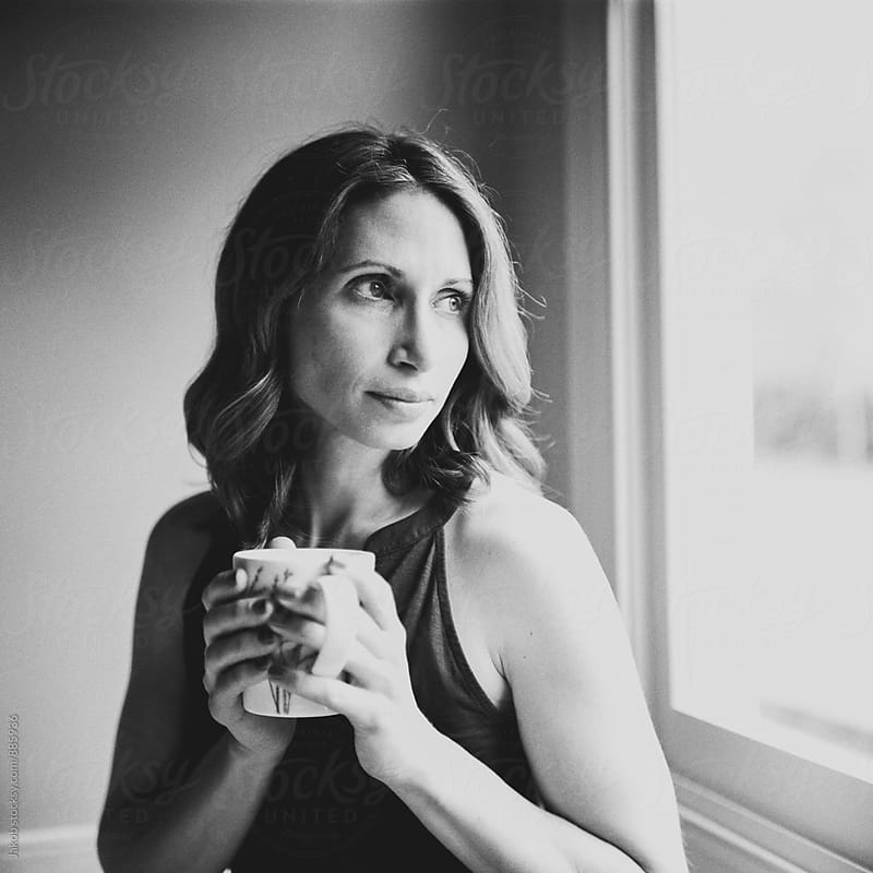 Beautiful woman looking out a window holding a cup of coffee by Jakob for Stocksy United