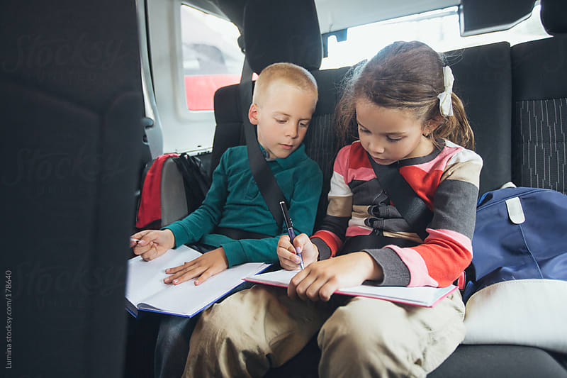 Boy and Girl Doing Homework in the Car by Lumina for Stocksy United
