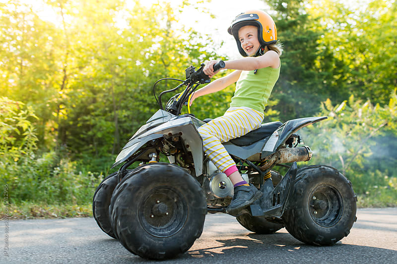 Fearless Girl Having Fun Riding Fast Gas Powered Kids ATV Quad On Trail With Sunflare on Cottage Road by JP Danko for Stocksy United