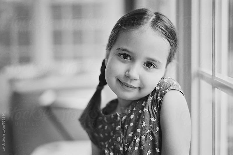 Black and white portrait of a cute young girl looking at camera by Jakob for Stocksy United