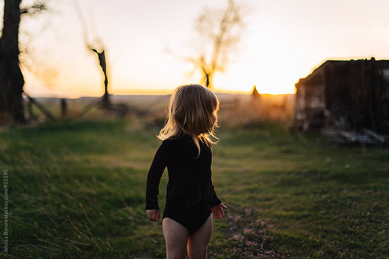 Toddler girl dancing outside at sunset. by Jessica Byrum for Stocksy United