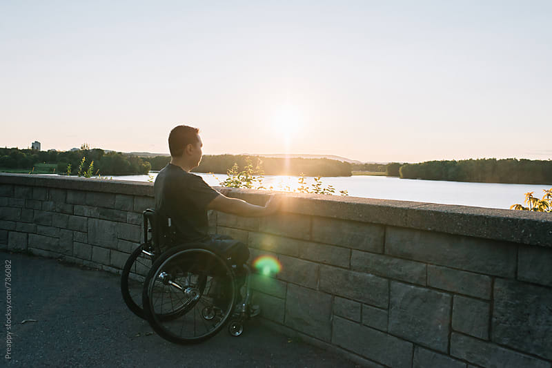 Man in wheel chair against brick wall by Preappy for Stocksy United