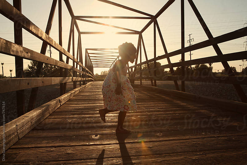 African American Girl Dancing on Wodden Bridge by Dina Giangregorio for Stocksy United