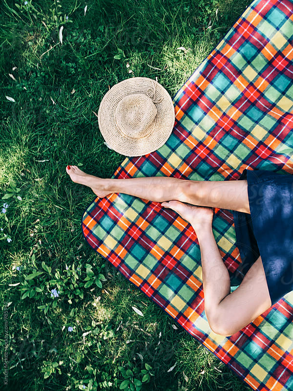 Lying on a picnic rug in the summer sun by Kirstin Mckee for Stocksy United