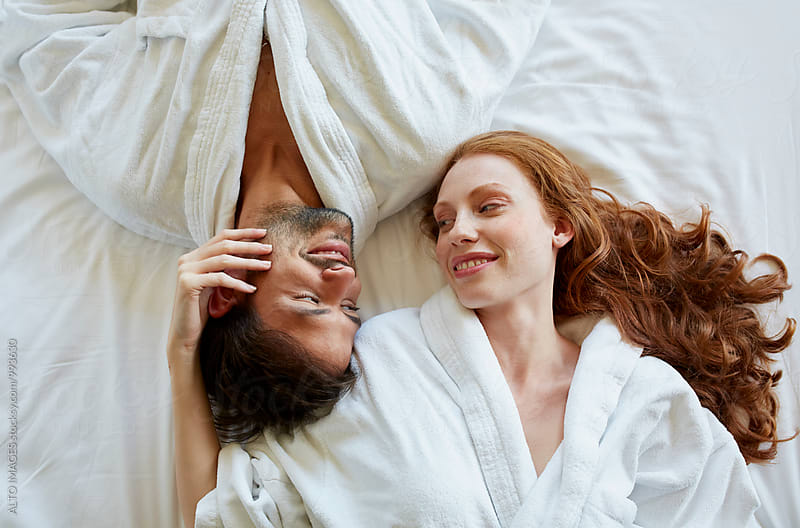 Romantic Couple Lying In Bed Of Hotel Room by ALTO IMAGES for Stocksy United
