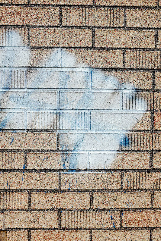 Paint covering graffiti markings on building wall, close up by Paul Edmondson for Stocksy United