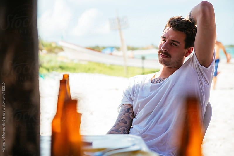 Young man with mustache strechting his arm and relaxing at a beach bar outside by Alejandro Moreno de Carlos for Stocksy United