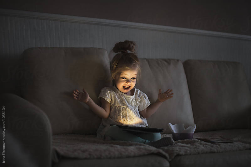 Little girl with tablet in a dark room