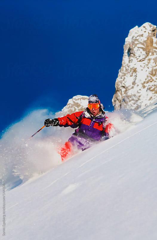 Young man in orange jacket skiing in powder snow in St Anton Austria by Soren Egeberg for Stocksy United