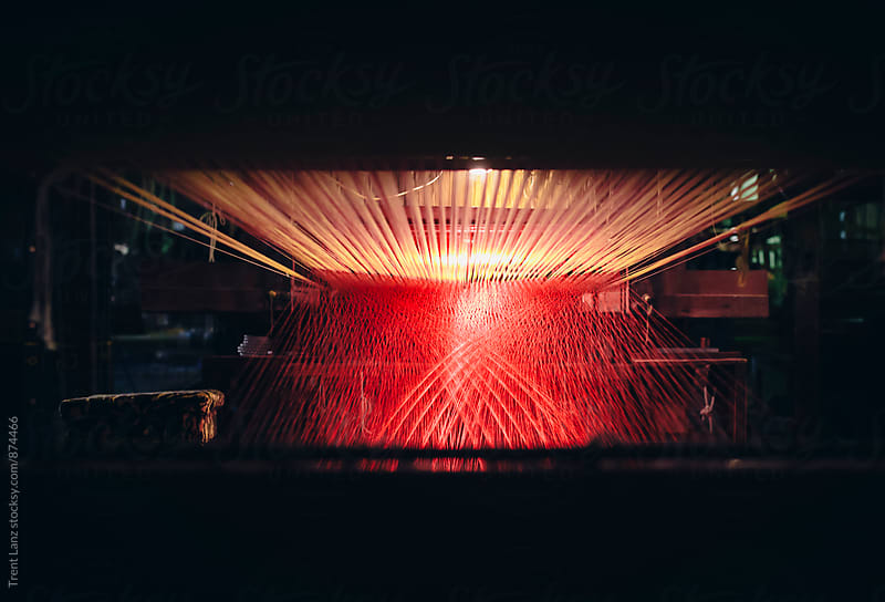 View on loom  with red and pink threads by Trent Lanz for Stocksy United