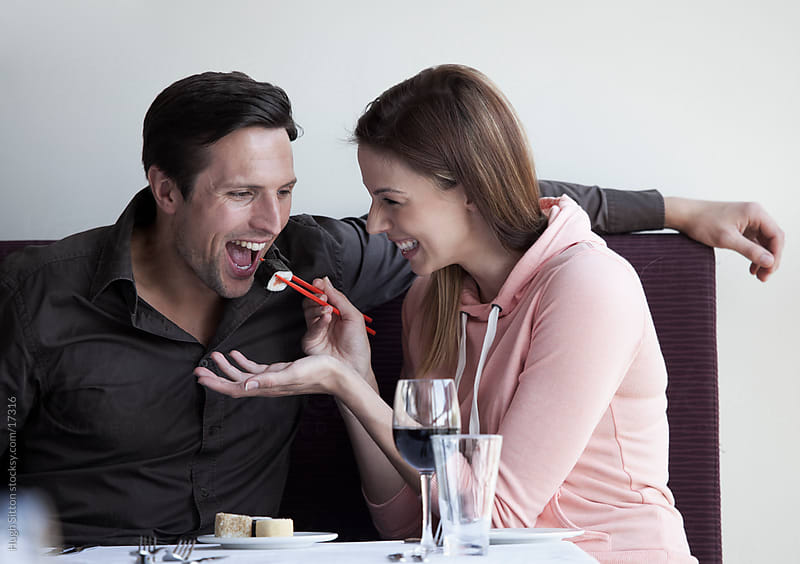 Couple sharing sushi in restaurant. by Hugh Sitton for Stocksy United
