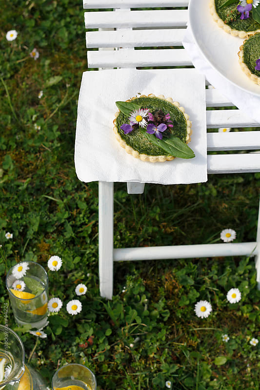 Spinach quiche with spring flowers on white table by Noemi Hauser for Stocksy United