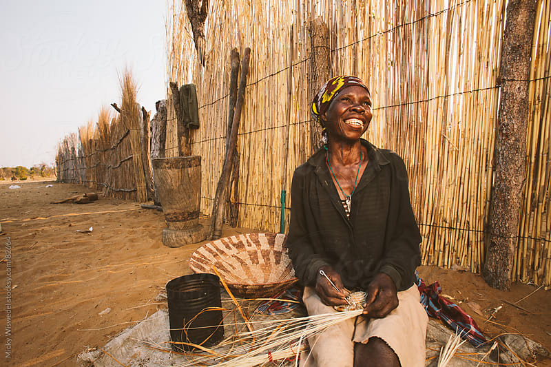 rural African Hambukushu woman weaving a reed basket by Micky Wiswedel for Stocksy United