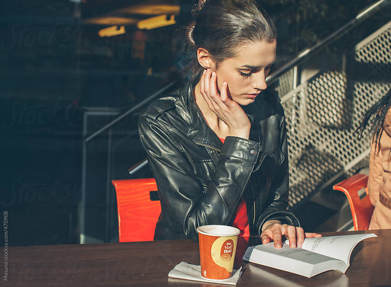 Young Woman Reading a Book in a Cafe  by Mosuno for Stocksy United