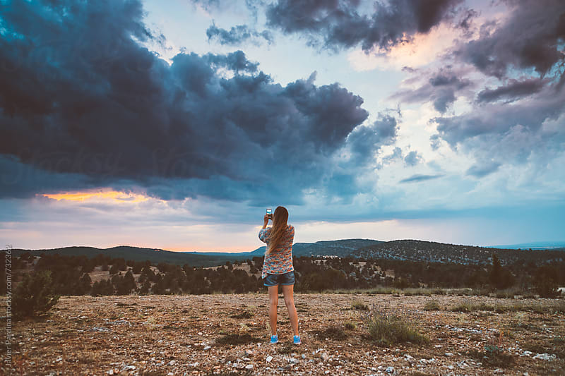 woman taking photos of sunset with smartphone by Javier Pardina for Stocksy United
