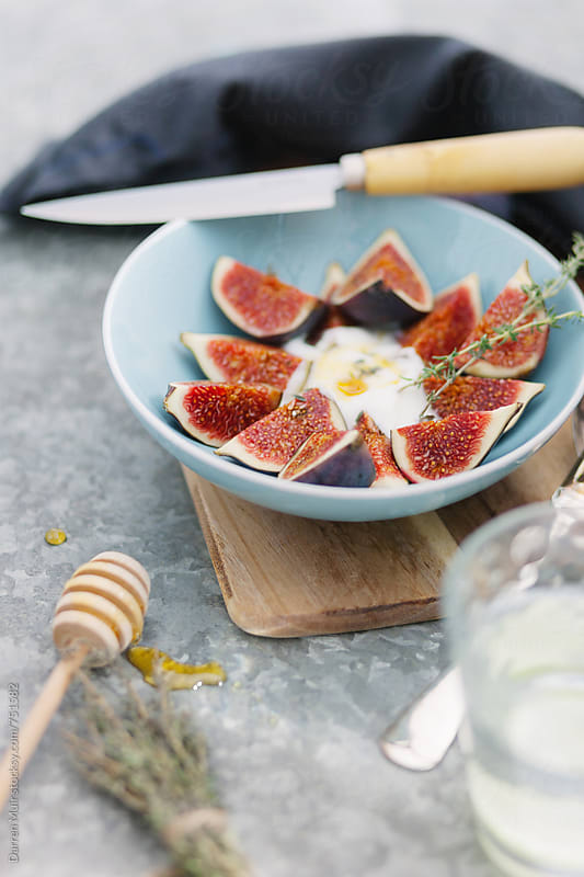 Figs in a blue bowl with yogurt and honey. by Darren Muir for Stocksy United