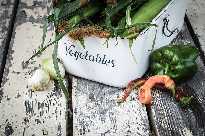Vintage enamelware vegetable bin with fresh vegetables by Rhonda Adkins for Stocksy United