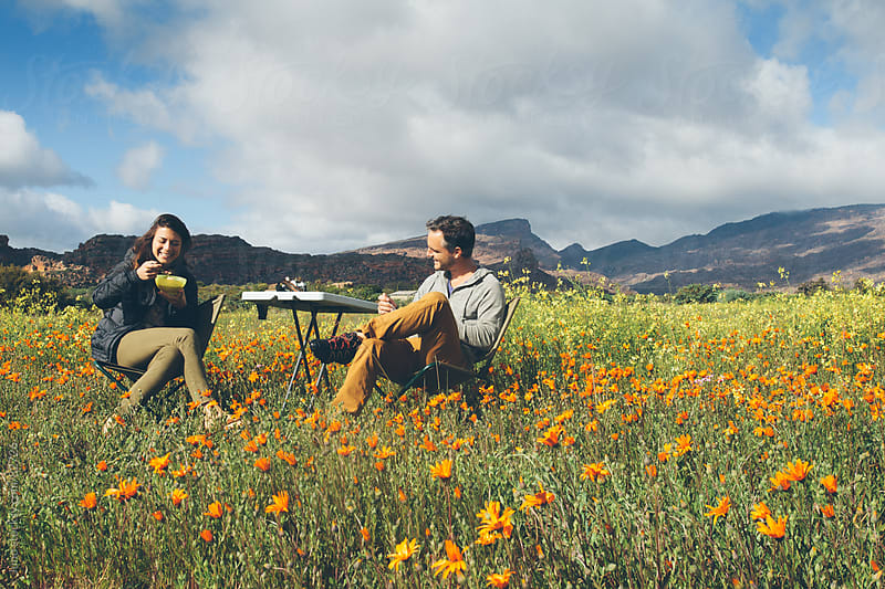 Couple enjoying breakfast picnic amongst flowers by Micky Wiswedel for Stocksy United