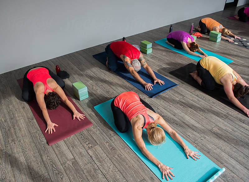 Class of yoga students in child pose by Cara Dolan for Stocksy United