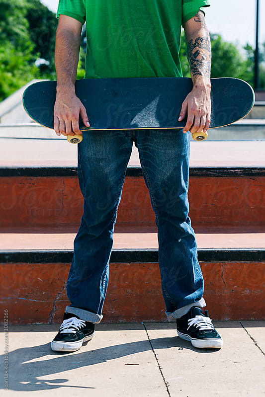 Skateboarder Holds Board In Front At Skate Park by Sean Locke for Stocksy United