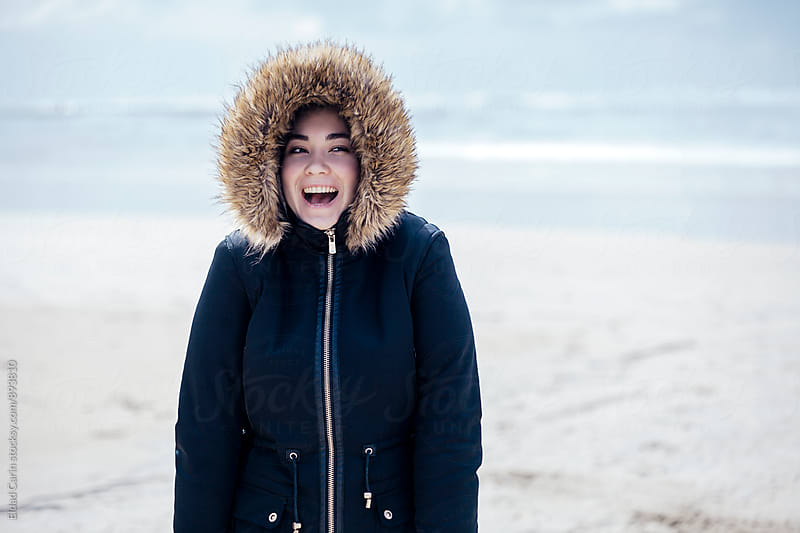 Young Woman Winter Beach Portrait by Eldad Carin for Stocksy United
