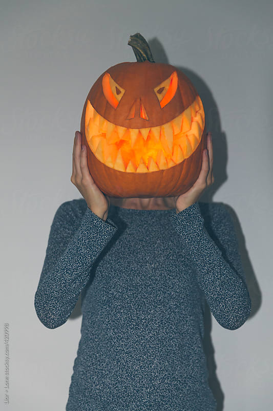 Woman holding glowing carved Halloween pumkin in front of her face by Lior + Lone for Stocksy United
