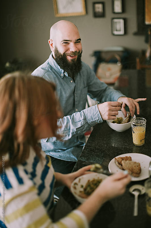 A Young Couple Eats Food Together in Their Kitchen - Lifestyle Food and Cooking by Rachel Gulotta Photography for Stocksy United
